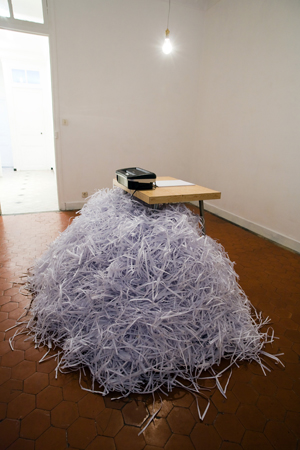 Alexandra Guillot, Silencio, 2009. Destructeur de documents, papier, table, broderie encadrée (31 x 22 cm), lumière.  © la Maison, galerie singulière. Photo : Nicolas Caluaud.